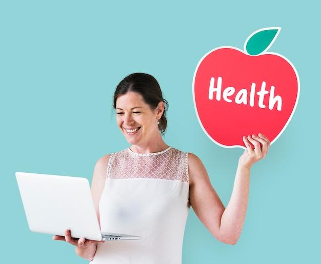Mujer sosteniendo un icono de salud y usando una laptop