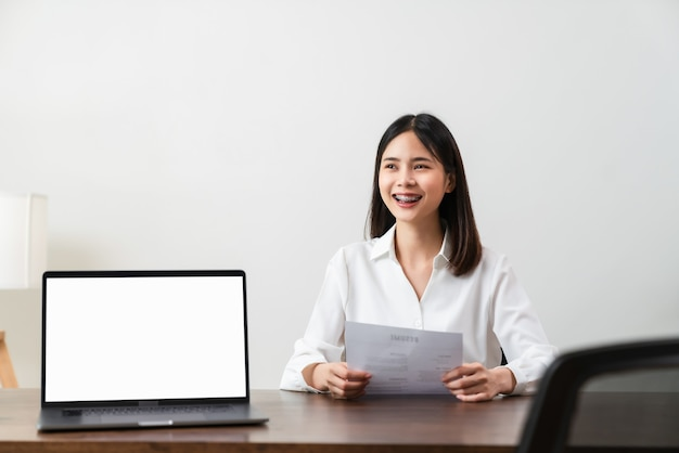 Mujer sosteniendo la información de la solicitud de currículum en la mesa cerca de la computadora portátil en blanco