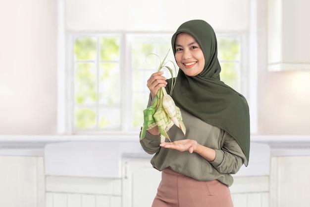 Mujer sosteniendo ketupat. mujer musulmana hijab con plato tradicional de pastel de arroz