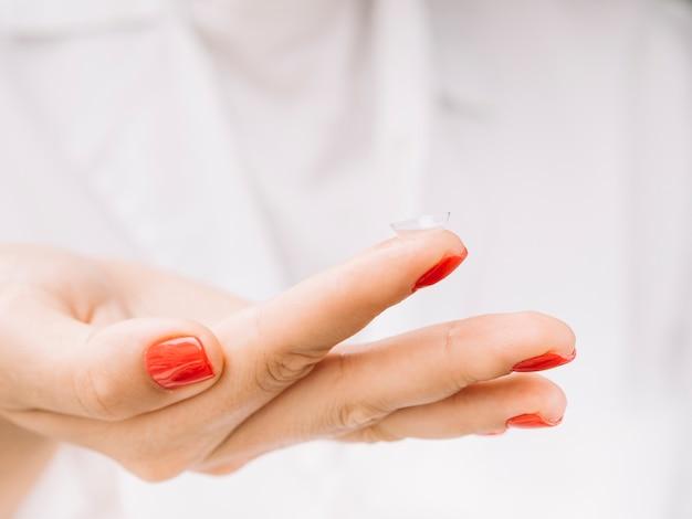 Mujer sosteniendo lentes de contacto en su dedo