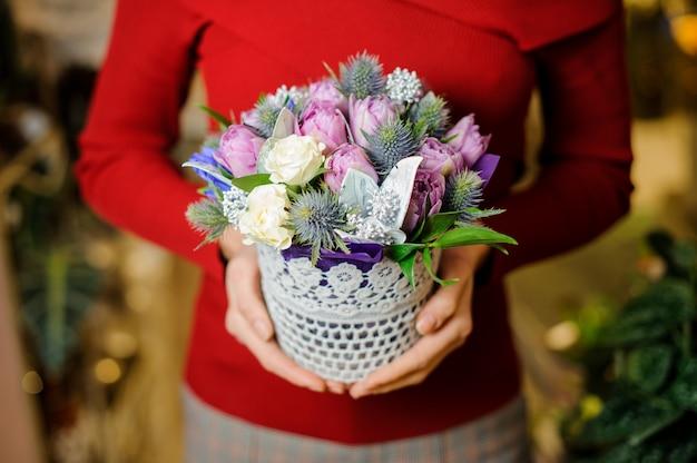 Mujer sosteniendo una linda olla pequeña con composición de flores para el día de san valentín