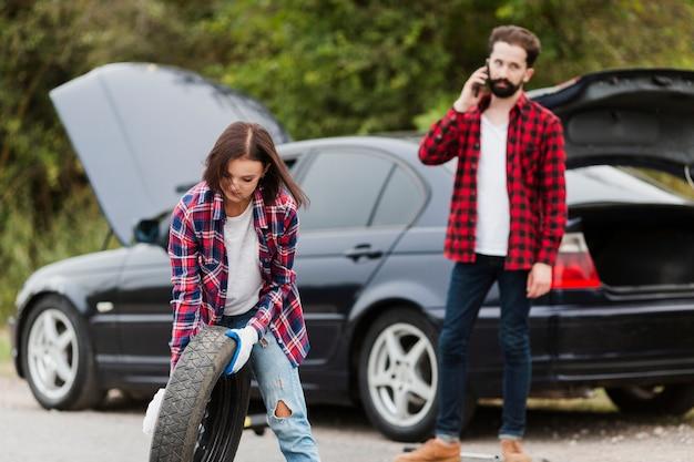 Mujer sosteniendo la llanta de refacción y el hombre hablando por teléfono