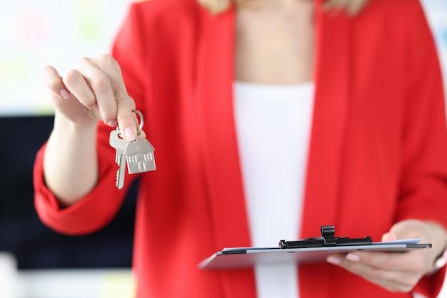 Mujer sosteniendo las llaves de la casa y el portapapeles con documentos en sus manos closeup inmobiliaria en