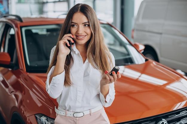 Mujer sosteniendo las llaves del coche por su coche nuevo