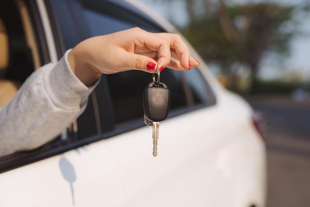 Mujer sosteniendo las llaves de encendido de un coche en su mano colgando a través de la ventana lateral abierta