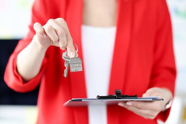 Mujer sosteniendo llaves de metal y documentos en el portapapeles en sus manos closeup