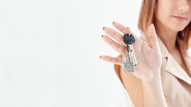 Mujer sosteniendo las llaves de su nueva casa con espacio de copia