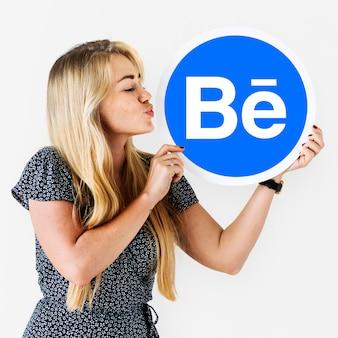 Mujer sosteniendo un logo de behance.