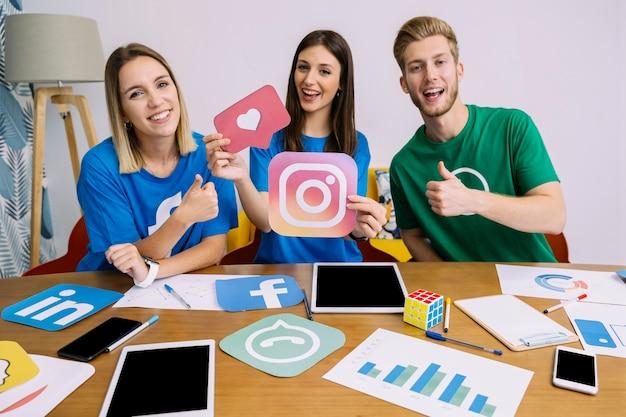 Mujer sosteniendo el logo de snapchat con sus amigos mostrando signo thumbup
