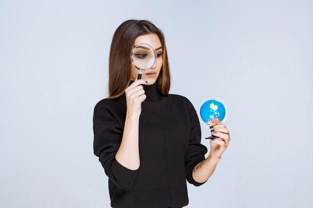 Mujer sosteniendo una lupa y comprobando el globo terráqueo.