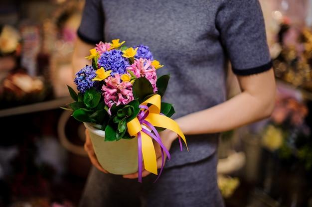 Mujer sosteniendo una maceta blanca con jacintos coloridos