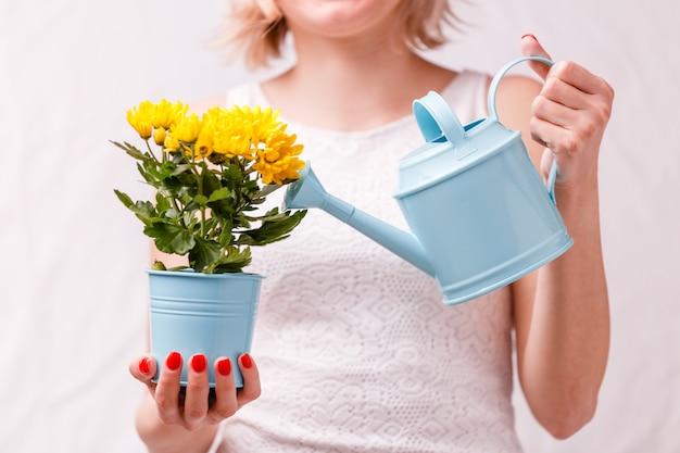 Mujer sosteniendo maceta con flor amarilla y regadera