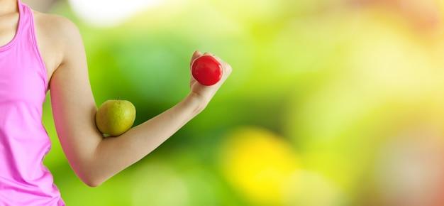 Una mujer sosteniendo una mancuerna roja para ejercicio y entrenamiento, manzana en un brazo