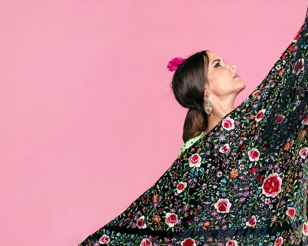 Mujer sosteniendo manila chal mirando hacia arriba
