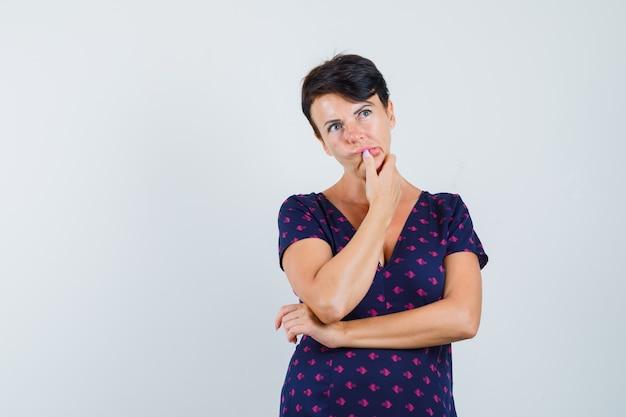 Mujer sosteniendo la mano en la barbilla en el vestido y mirando indeciso