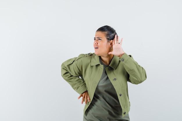 Mujer sosteniendo la mano cerca de la oreja en chaqueta, camiseta y mirando curiosa.
