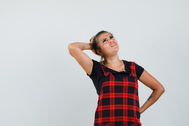 Mujer sosteniendo la mano detrás de la cabeza en vestido delantal y mirando pensativa. vista frontal.