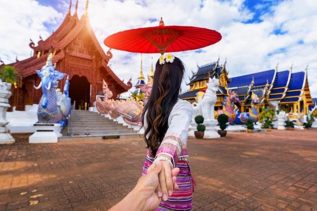 Mujer sosteniendo la mano del hombre y llevándolo al templo en chiang mai.