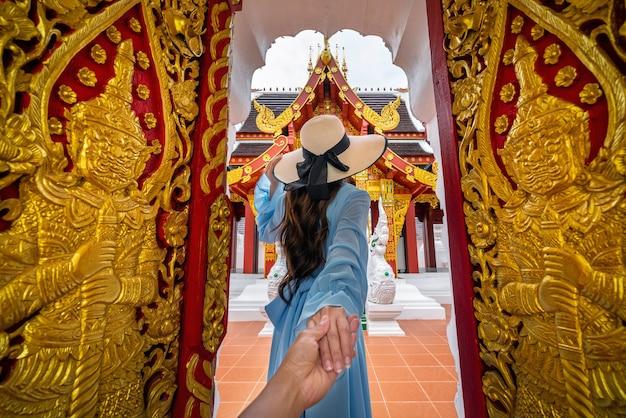 Mujer sosteniendo la mano del hombre y llevándolo a wat khua khrae en chiang rai, tailandia
