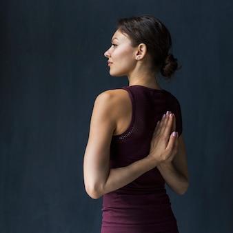 Mujer sosteniendo la mano en una pose de oración detrás de su espalda