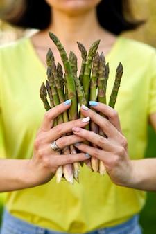 Mujer sosteniendo un manojo de espárragos verdes en sus manos al aire libre, lanzas de espárragos verdes frescos al sol, espacio de copia para texto. cosecha, lista para cocinar, dieta vegana saludable, comida local.