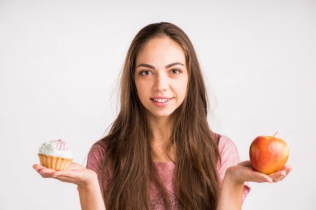 Mujer sosteniendo y manzana y un cupcake