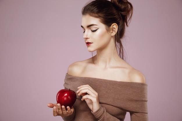 Mujer sosteniendo manzana roja en rosa