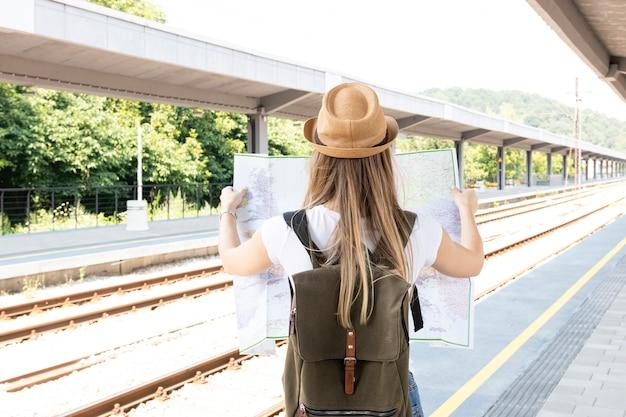 Mujer sosteniendo un mapa desde atrás