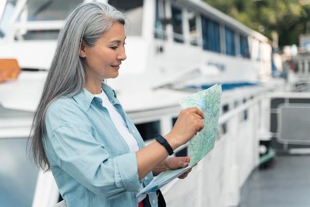 Mujer sosteniendo mapa plano medio