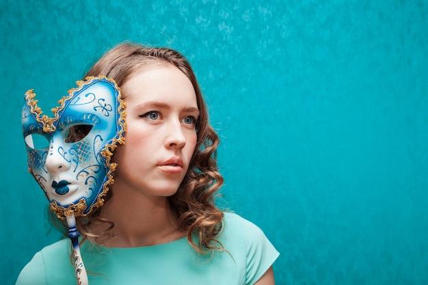 Mujer sosteniendo una máscara de carnaval brasileño