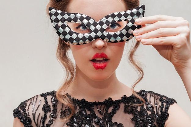 Mujer sosteniendo una máscara de carnaval con su mano