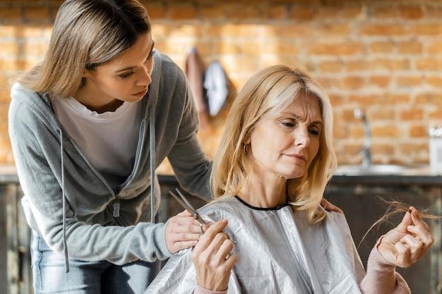 Mujer sosteniendo mechón de pelo y tijeras