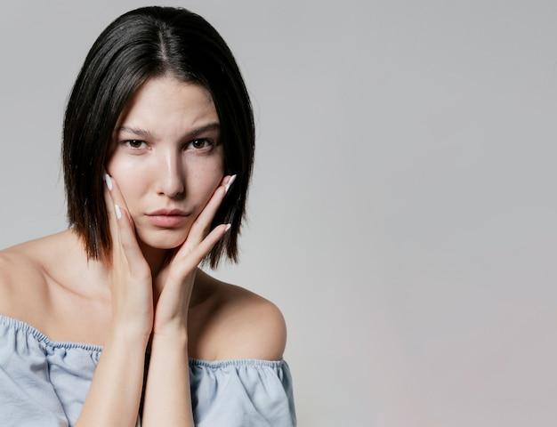 Mujer sosteniendo las mejillas mientras posa