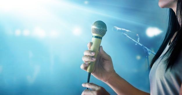 Mujer sosteniendo el micrófono y cantando en el escenario de concierto