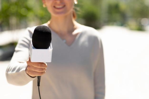 Mujer sosteniendo un micrófono para una entrevista
