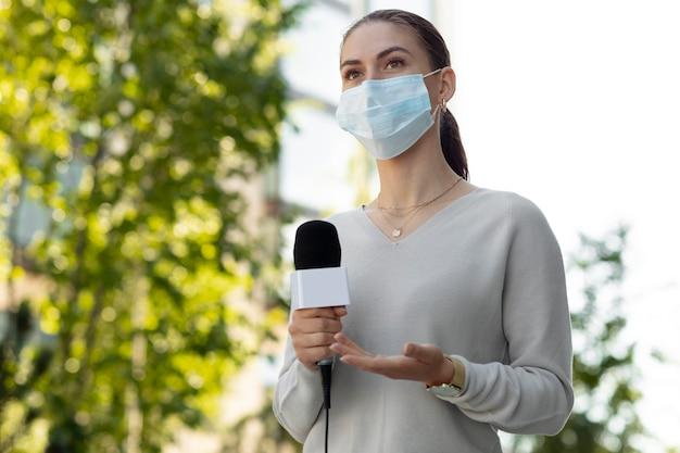 Mujer sosteniendo un micrófono mientras usa una máscara médica