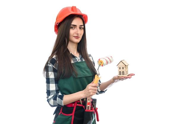 Mujer sosteniendo modelo de casa y rodillo aislado en blanco