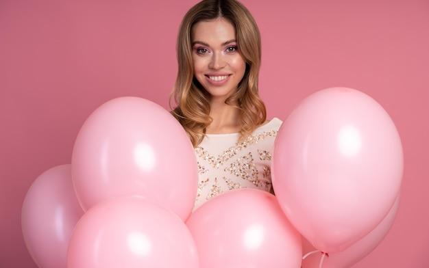 Mujer sosteniendo un montón de globos