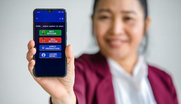 Mujer sosteniendo y mostrando pantallas de teléfonos inteligentes con botones para comprar y vender en una aplicación para comercio de dinero digital bitcoin o criptomoneda.