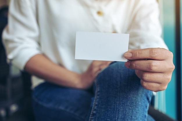 Una mujer sosteniendo y mostrando una tarjeta de presentación vacía en blanco a alguien