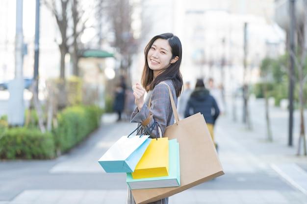 Una mujer sosteniendo muchas bolsas de compras