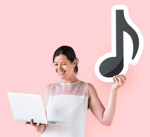 Mujer sosteniendo una nota musical y una computadora portátil