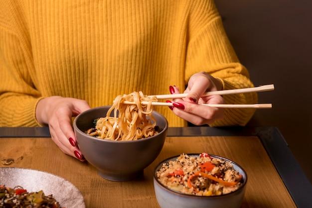 Mujer sosteniendo palillos con fideos en la mesa