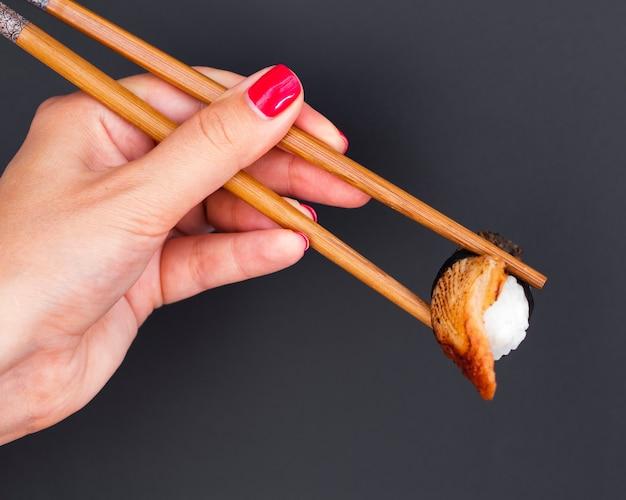 Mujer sosteniendo en palillos de madera un sushi
