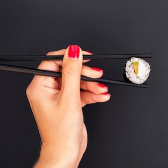Mujer sosteniendo palillos con rollo de sushi
