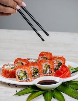 Mujer sosteniendo palillos para tomar rollos de sushi con tobiko rojo