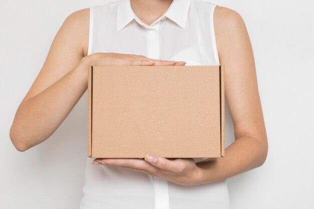 Mujer sosteniendo un paquete de cartón en sus manos