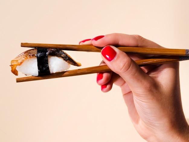 Mujer sosteniendo en un par de palillos un sushi sobre un fondo rosa pálido