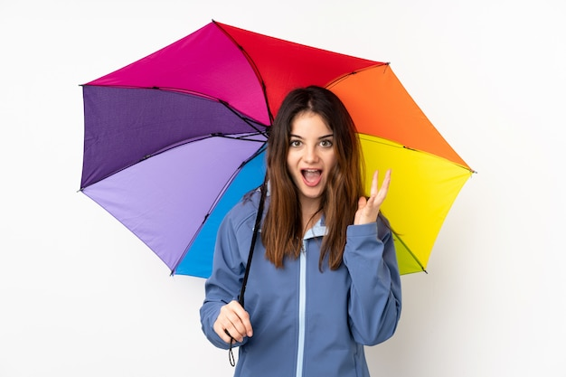 Mujer sosteniendo un paraguas aislado en la pared blanca con expresión facial sorpresa