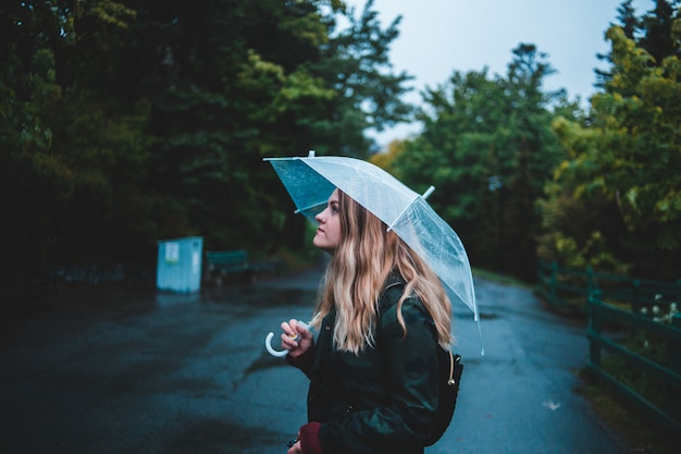 Mujer sosteniendo paraguas estando en medio de la carretera